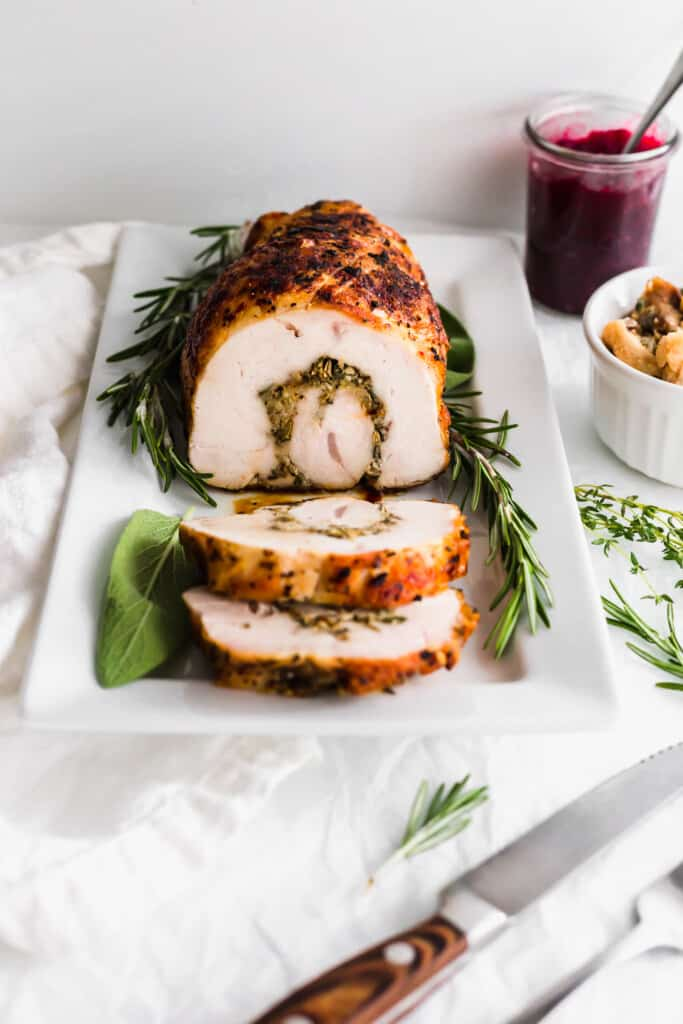Sliced turkey roulade on a white rectangular plate with herbs surrounding it, knife and fork, cranberry sauce and stuffing on the side.