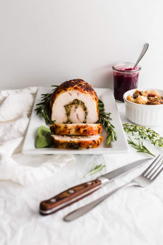 Turkey roulade on a white rectangular plate with herbs surrounding it, knife and fork, cranberry sauce and stuffing on the side.