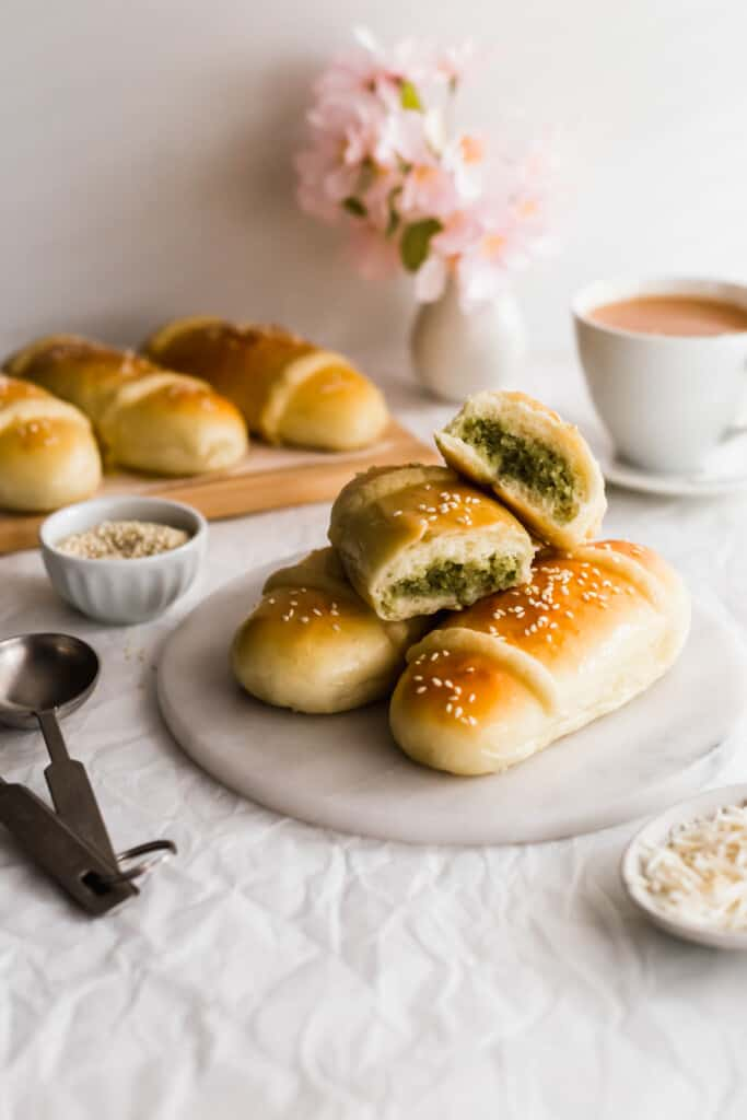 A cut matcha coconut bun revealing filling on a stack of coconut buns on marble trivet, cup of tea in background.