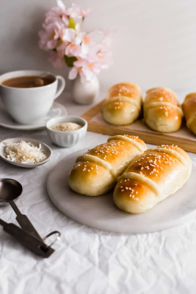 Coconut buns on marble trivet, coconut flakes, sesame seeds in bowl, cup of tea in background.