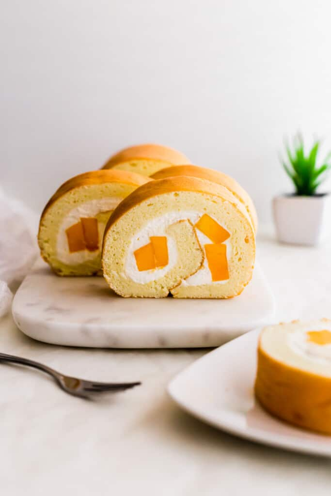 Close up of yellow roll cake with white cream and mango pieces.