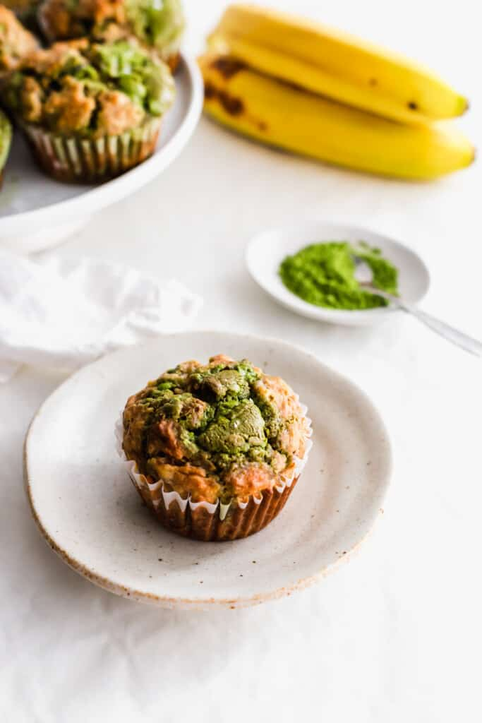 Matcha banana muffin on a small plate with matcha powder and bananas in the background.