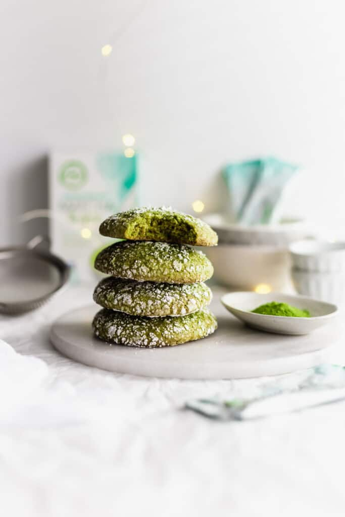 Stack of matcha crinkle cookies on marble trivet, with tea packaging in background.