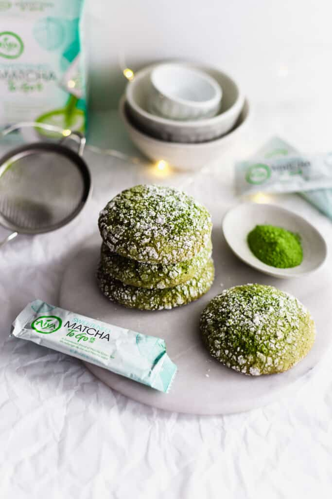 Matcha crinkle cookies on marble trivet, with tea packaging, festive lights in background.