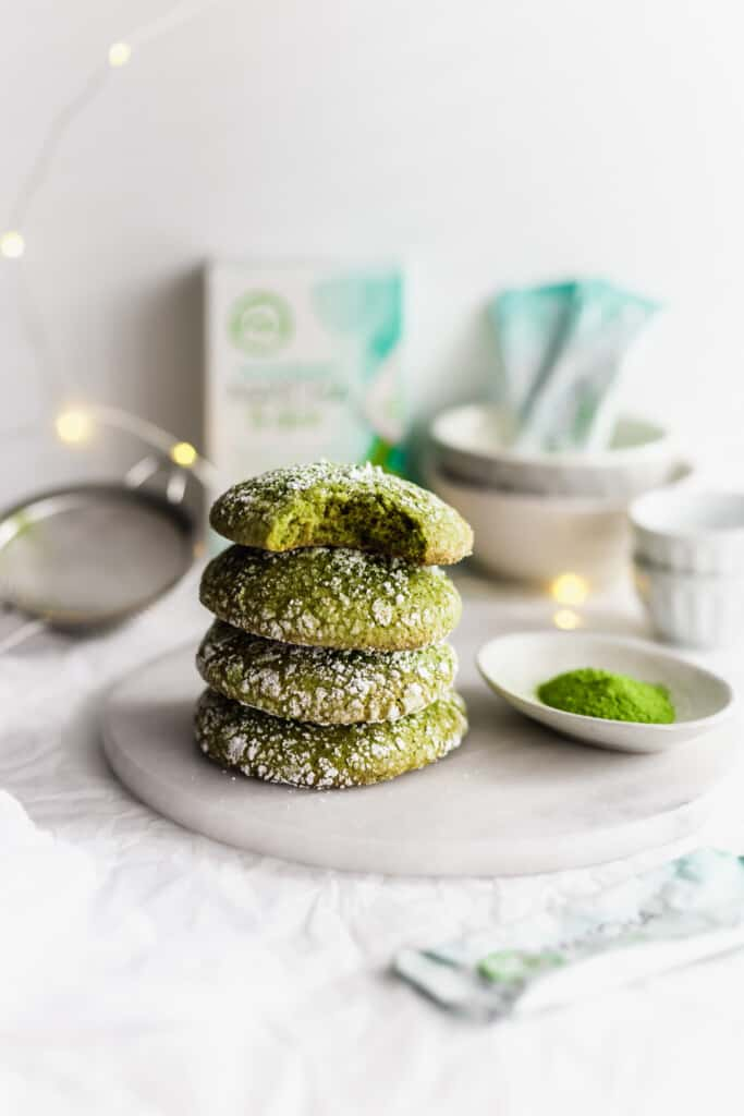 Stack of matcha crinkle cookies on marble trivet, with packaging, festive lights in background.