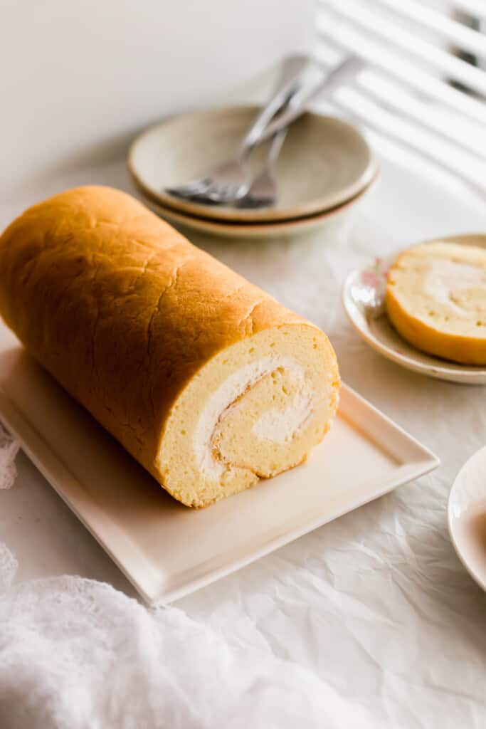 Close up of uncut yellow swiss roll cake with white cream on a rectangular plate, plates with forks in the background.