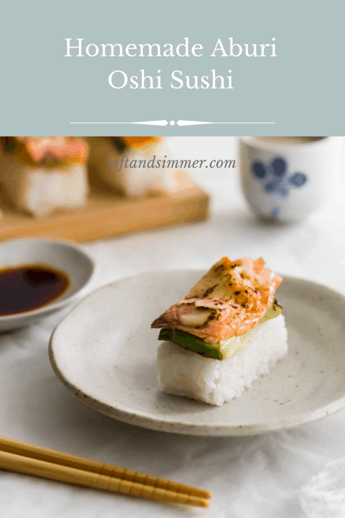 Aburi salmon sushi on beige plate with text overlay.