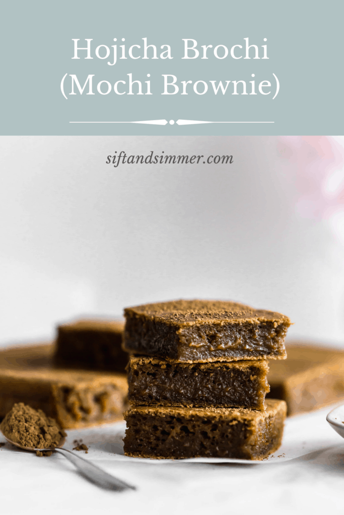 A stack of hojicha brownie mochi on parchment with a spoonful of hojicha powder on the side with text overlay.