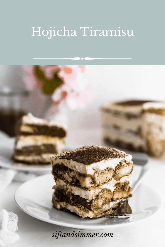 A slice of hojicha tiramisu on a white plate with fork with tiramisu container in the background.