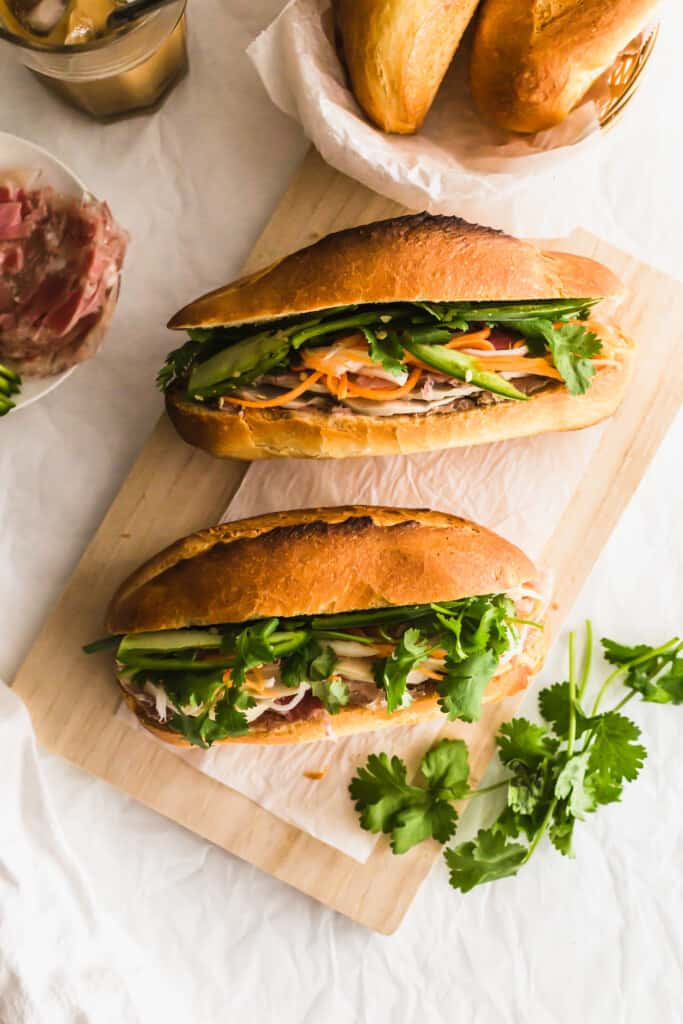 Banh mi sandwiches on wooden board, cilantro on the side.