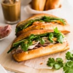 Banh mi sandwiches on wooden board, with coffee and baguettes in background.