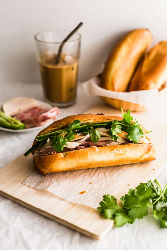 A banh mi sandwich on wooden board, with coffee and baguettes in background.