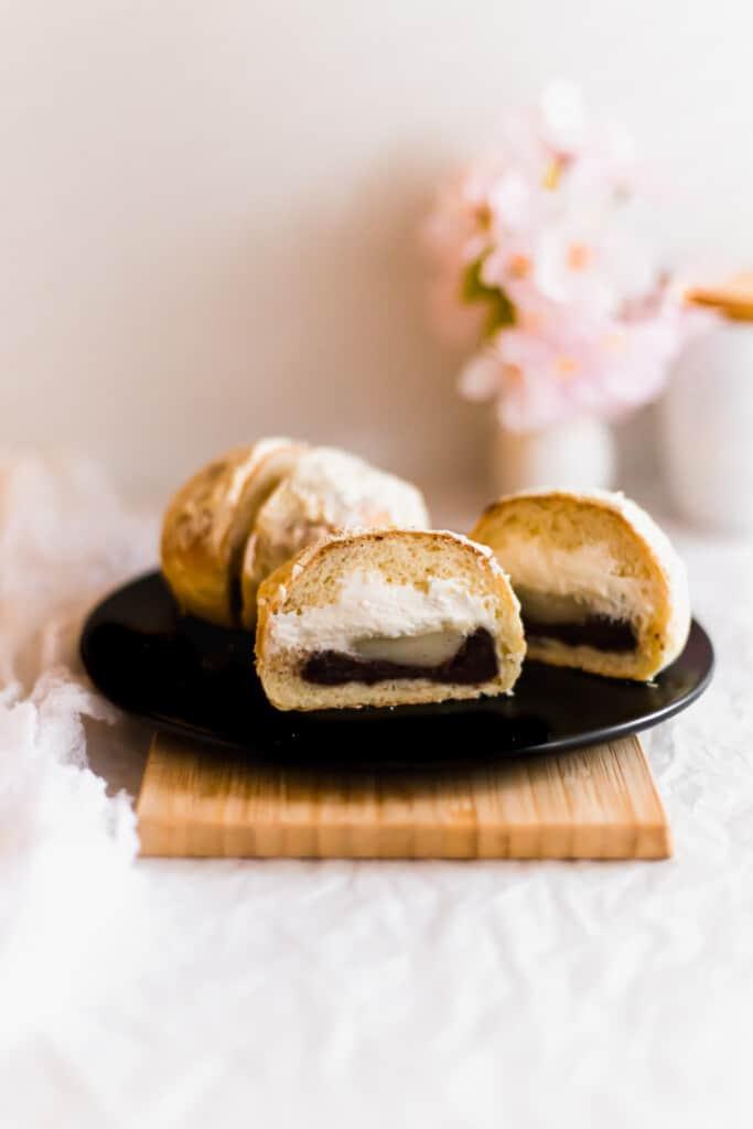 Cut Injeolmi cream buns on round black plate on wooden board.