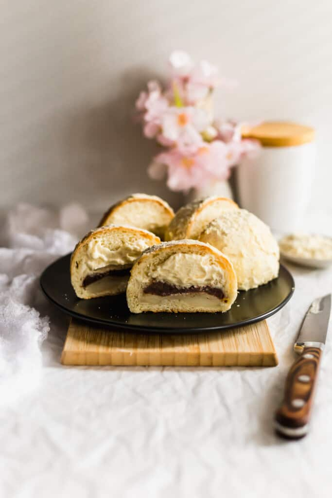 Cut Injeolmi cream buns with red bean paste and mochi on round black plate on wooden board.