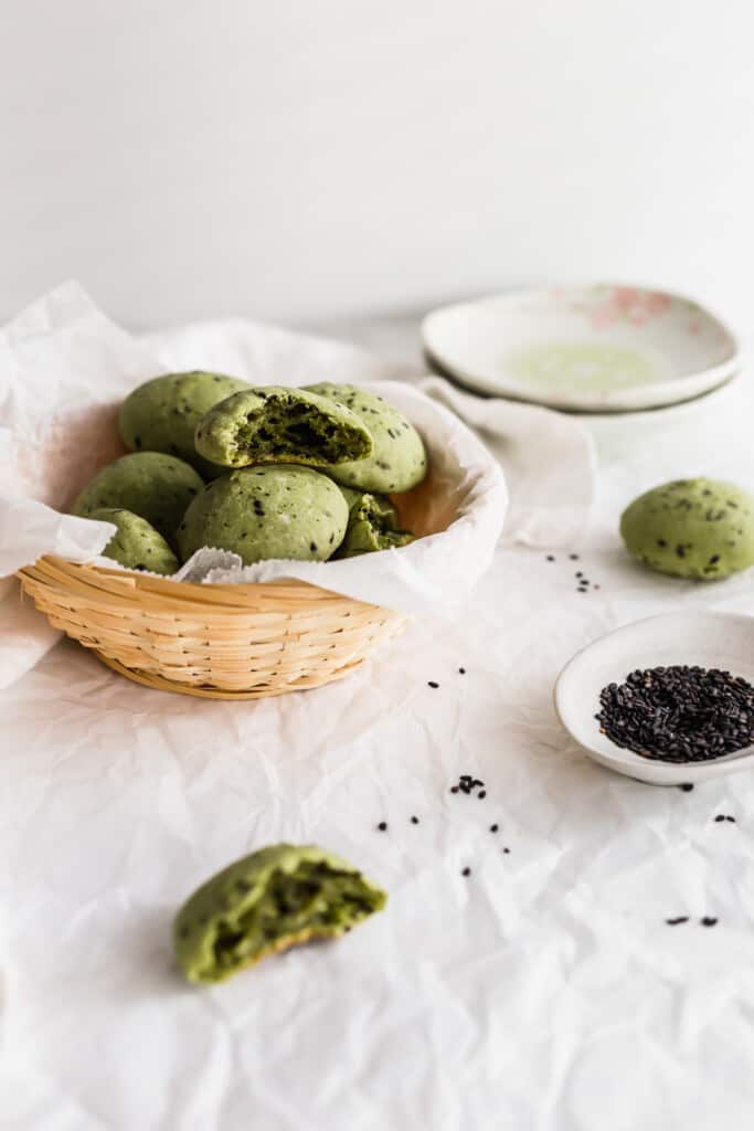 A basket of green matcha mochi bread with black sesame seeds.