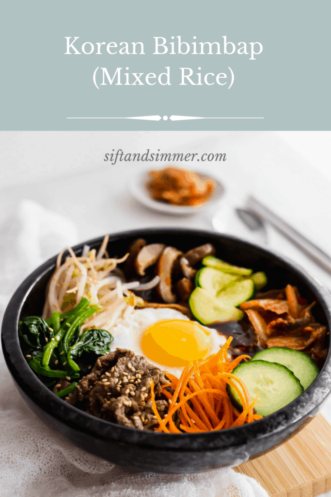 Close up of Korean bibimbap in a black bowl on wooden board with text overlay.
