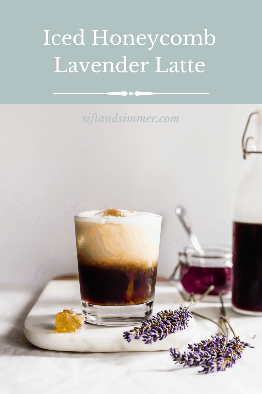 Glass of layered iced honeycomb lavender latte on marble with honeycomb and lavender flowers laying on the side, purple lavender syrup in background with text overlay.