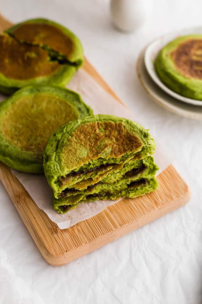 Stack of matcha hotteok on wooden board.