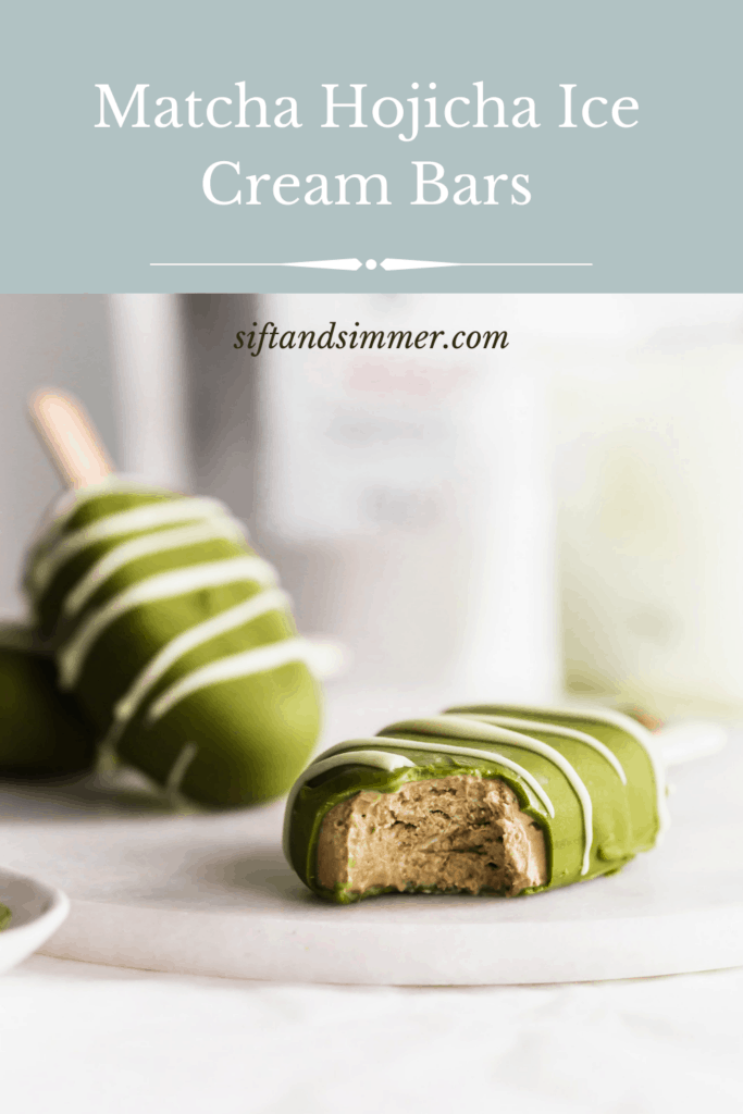 A matcha hojicha ice cream bar with a bite taken out of it on a marble trivet, ice cream bar and tea packaging in the background with text overlay.