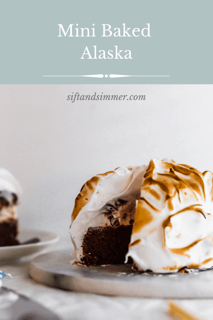 A mini baked Alaksa with chocolate cake and torched meringue with a piece cut out with text overlay.