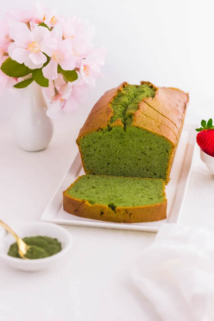 Sliced matcha pound cake loaf on white rectangular plate.