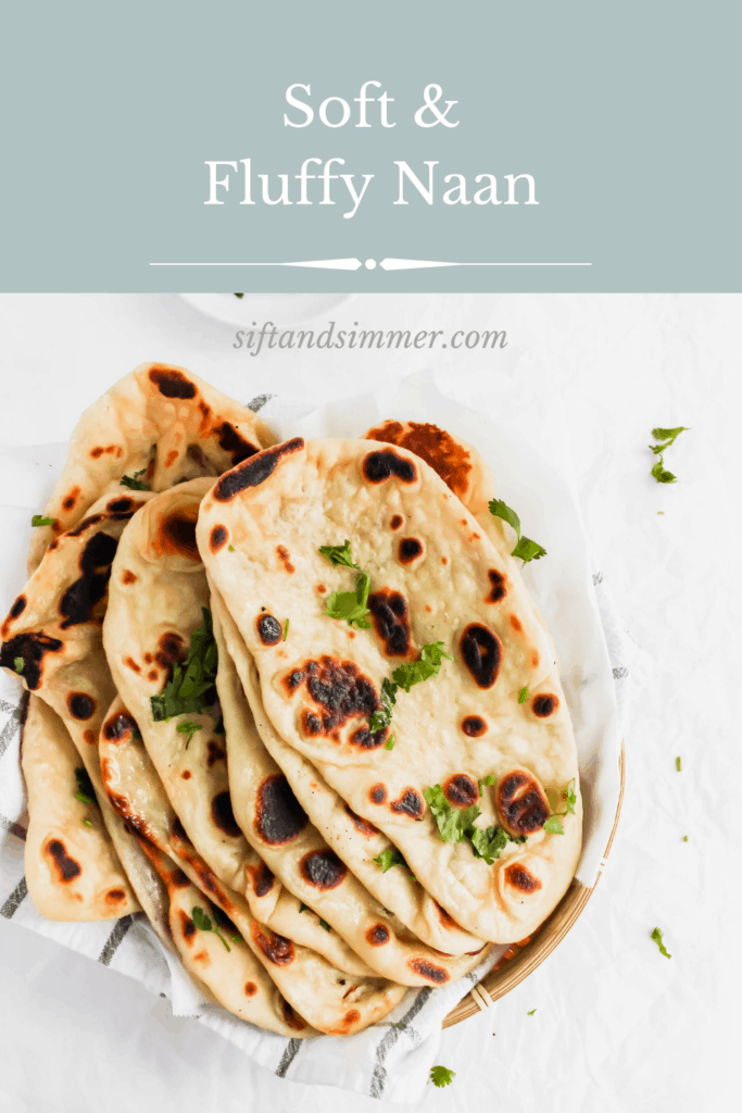 Soft & Fluffy Naan on a kitchen towel with cilantro sprinkled around with text overlay.