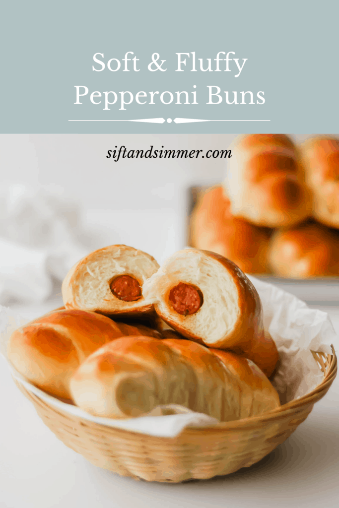 A basket of pepperoni buns with a bun cut in half to reveal the interior, tray of buns in background with text overlay.