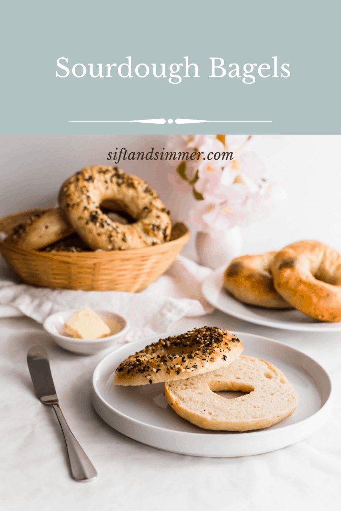 A sliced sourdough bagel on a white plate with knife on side, butter, bagels in basket and on a plate in background with text overlay.