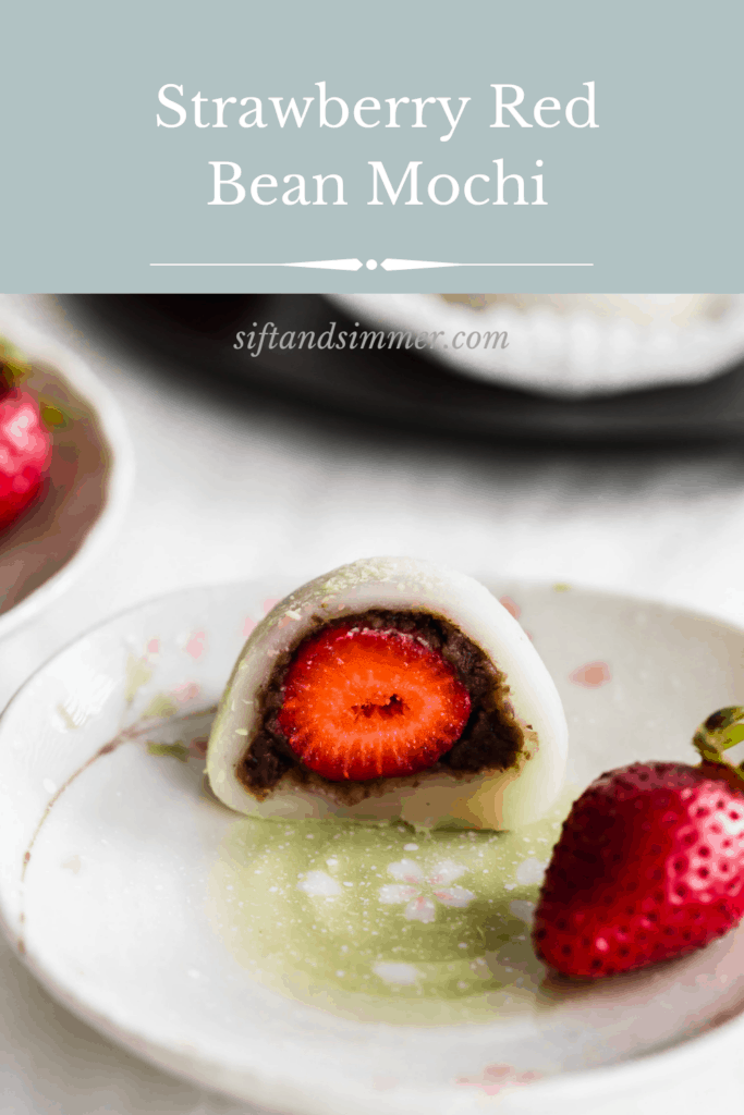 A closeup of cut open white mochi with red bean paste and strawberry with text overlay.