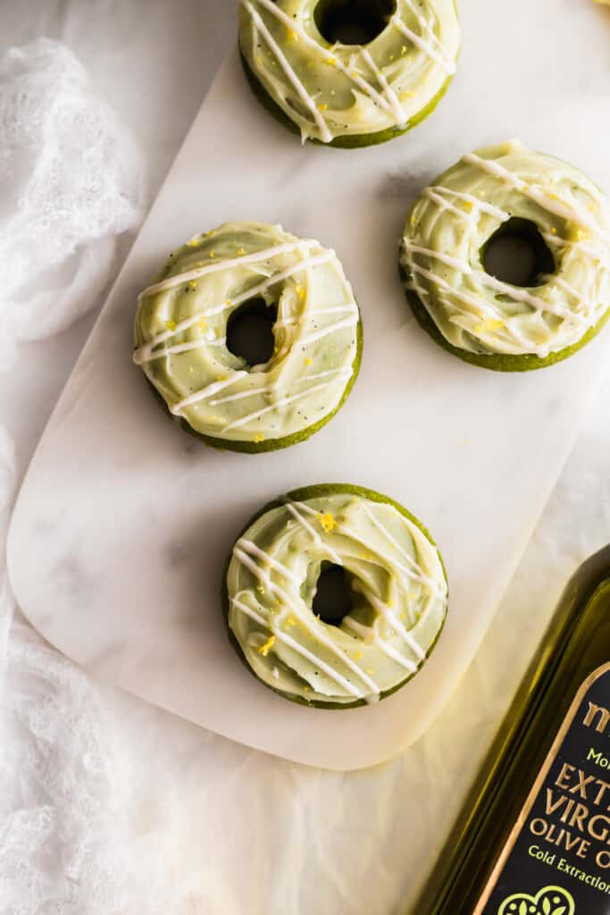 Matcha yuzu olive oil doughnuts on a white marble board with bottle of olive oil on the side.