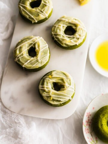 Matcha yuzu olive oil doughnuts on a white marble board with olive oil on the side.