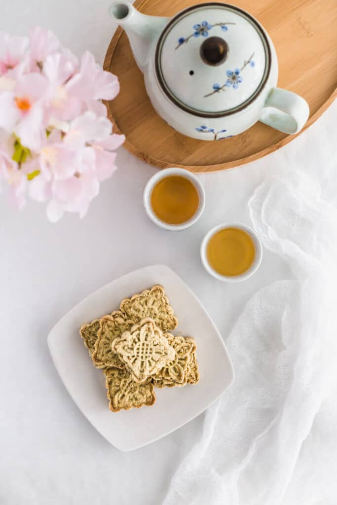 Almond cookies on a white plate with tea cups.