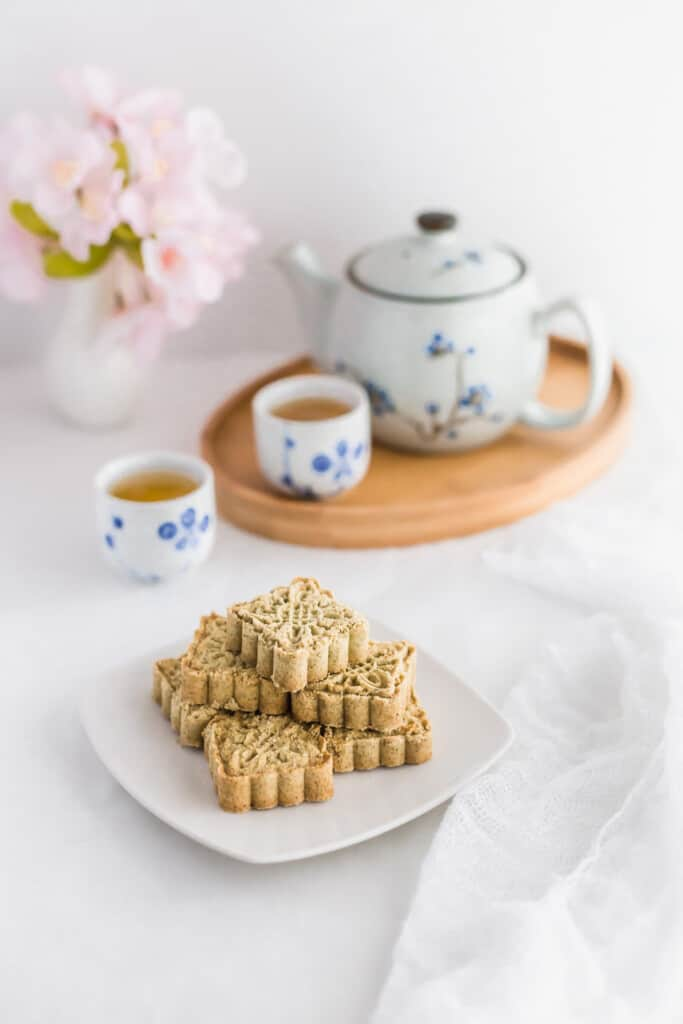 Almond cookies on a white plate with tea in the background.