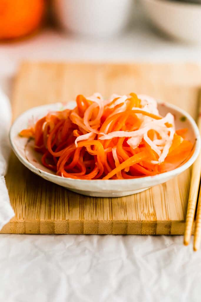 Close up of pickled daikon and carrot on a small plate on wooden board.