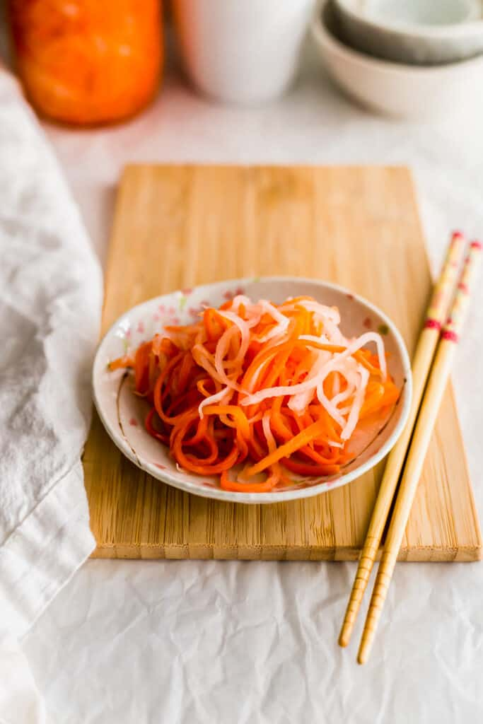 Pickled daikon and carrot on a small plate on wooden board with chopsticks on side.