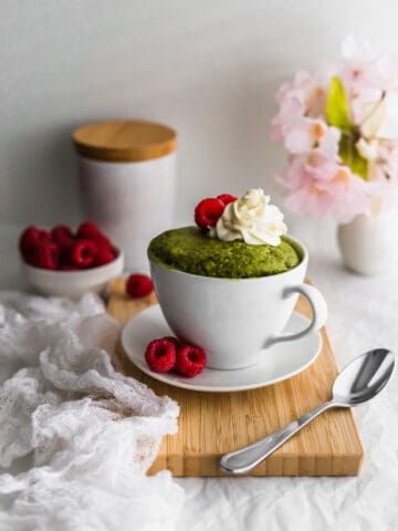 Matcha mug cake in a white mug with whipped cream and raspberries on a wooden board.