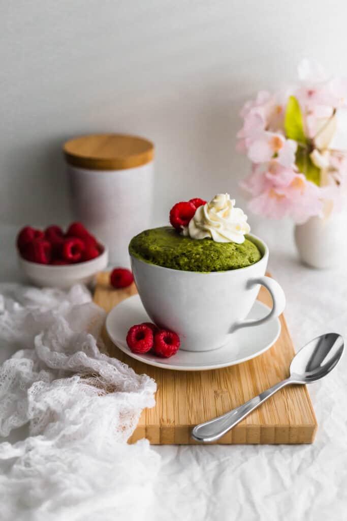 Matcha mug cake in a white mug with whipped cream and raspberries on a wooden board.
