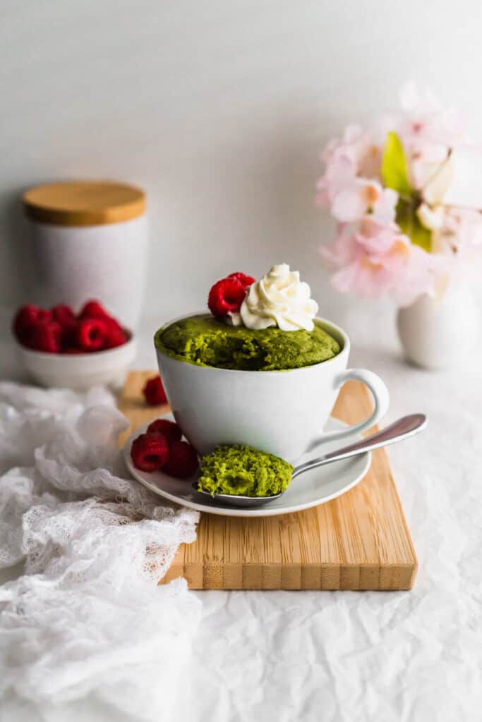 Matcha mug cake with a scoop of cake on a spoon.