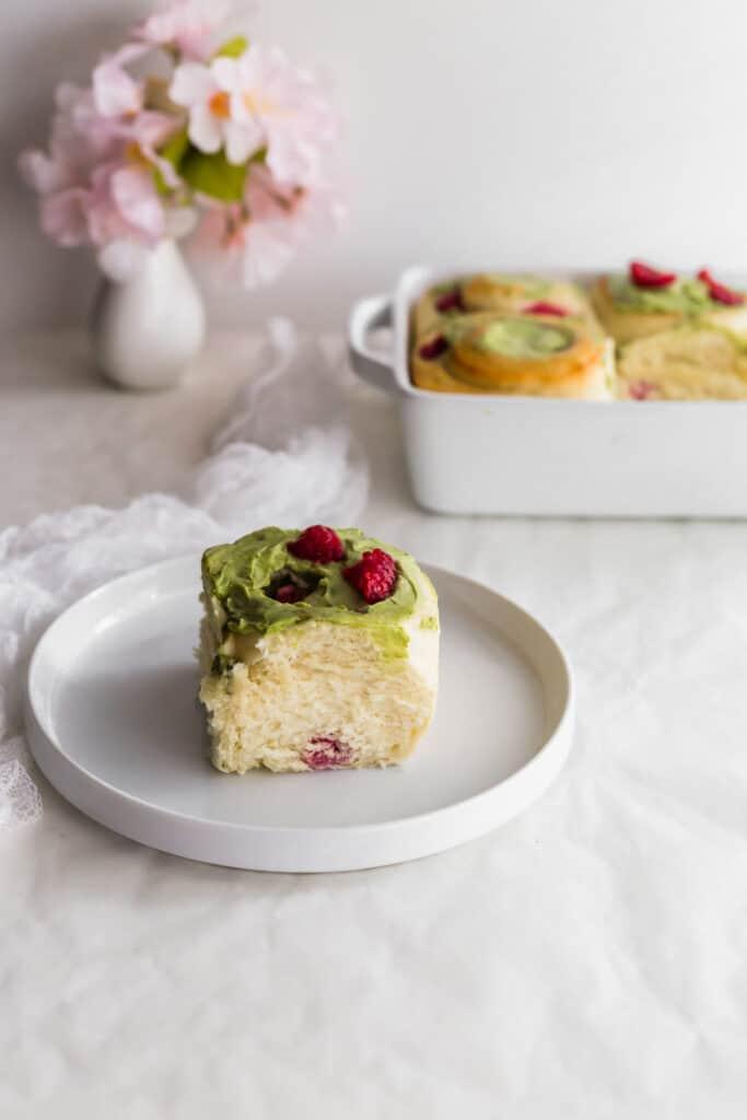 Matcha Raspberry Cream Cheese Roll on white round plate.