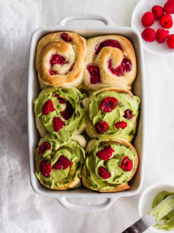 Overhead shot of Matcha Raspberry Cream Cheese Rolls in white baking dish.