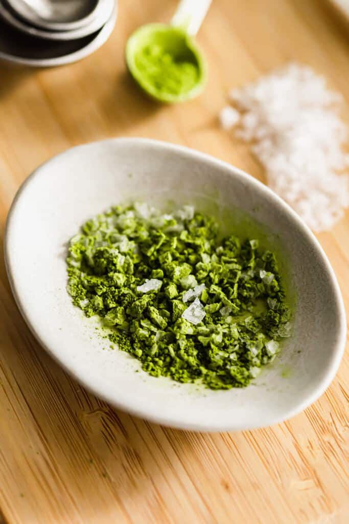 Close up of matcha salt in a dish on wooden board.