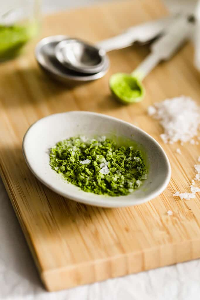 Close up of matcha salt in a dish on wooden board, salt granules and matcha in background.