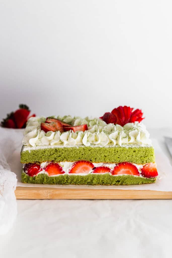 Unsliced matcha strawberry shortcake on wooden board.