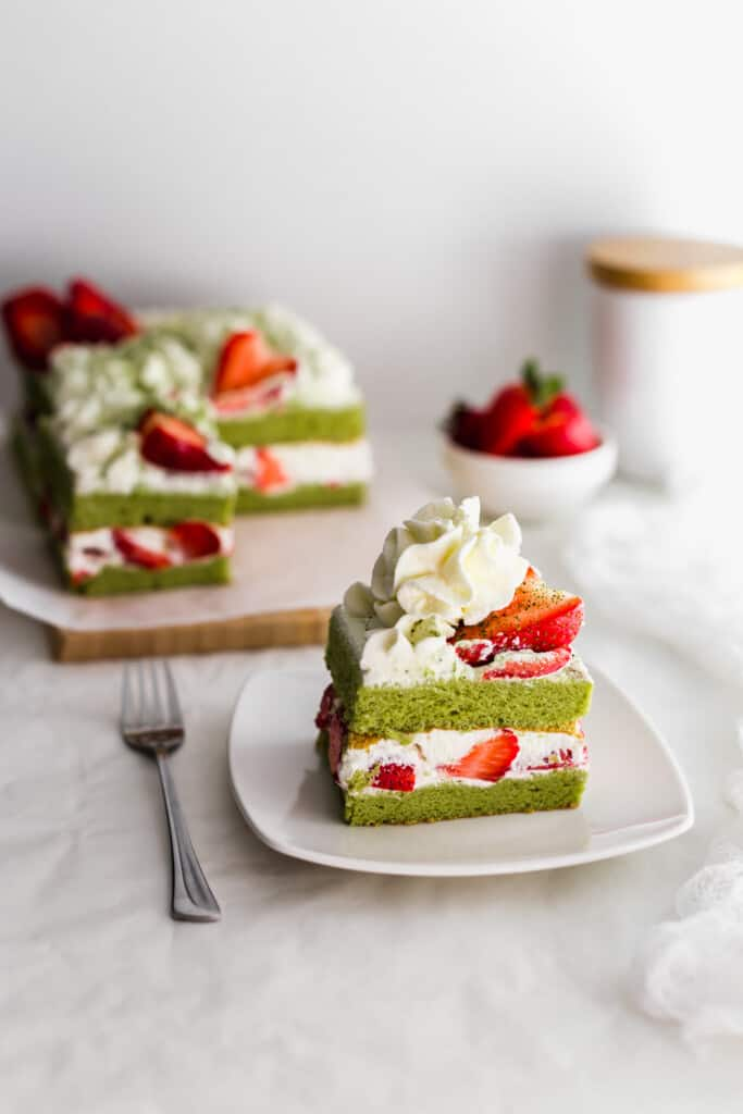 Slice of matcha strawberry shortcake on white plate with fork on side, cake in background.