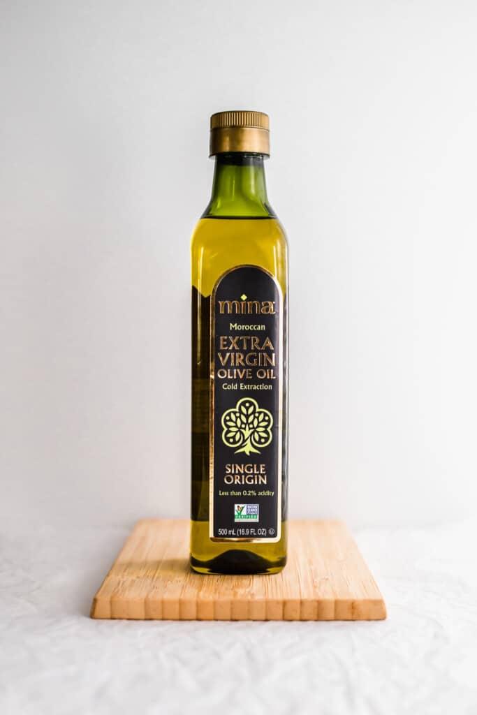 Bottle of Mina olive oil on wooden board.