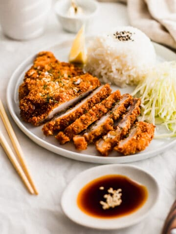 Plate of sliced pork tonkatsu with rice and shredded cabbage, and soy sauce in small dish.