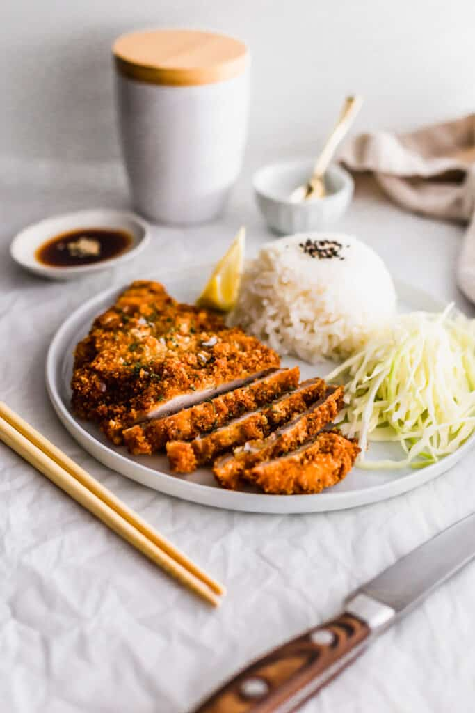 Plate of sliced pork tonkatsu with rice and shredded cabbage.