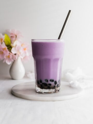 Glass of purple taro milk bubble tea with stainless steel straw on marble trivet