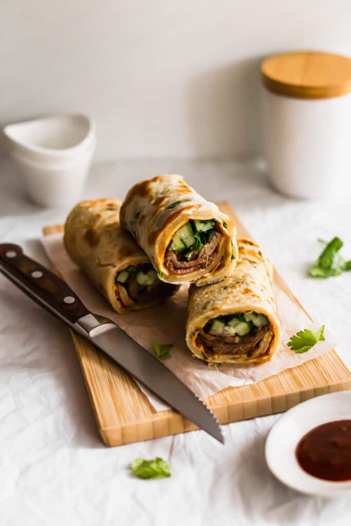 Beef pancake rolls on wooden board with knife.