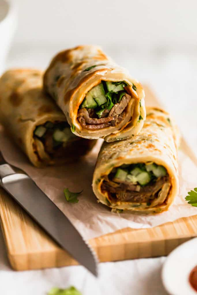 Close up of stacked green onion beef pancake rolls on wooden board.